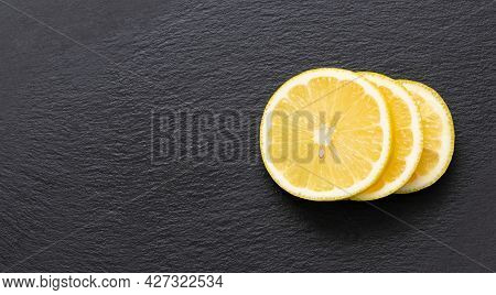 Sliced Lemon On A Dark Stone Background. Juicy Slices Of Citrus Fruit On A Gray Background. Copy Spa