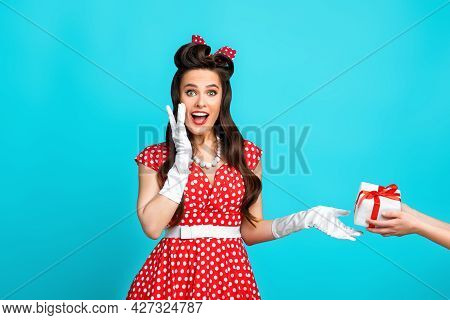 Excited Young Pinup Lady In Retro Dress Receiving Wrapped Gift Box For Holiday On Blue Studio Backgr