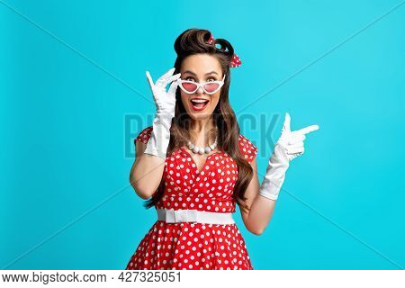 Cheerful Young Pinup Woman In Polka Dot Dress Touching Sunglasses, Pointing Aside On Blue Background