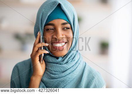 Closeup Of Smiling Black Islamic Lady In Hijab Talking On Mobile Phone
