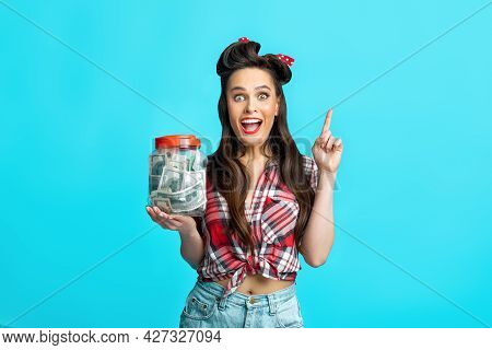 Money Savings Concept. Cheerful Young Pinup Woman Holding Jar Of Dollars, Pointing Upwards Over Blue