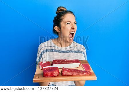 Young blonde woman holding board with raw meat angry and mad screaming frustrated and furious, shouting with anger. rage and aggressive concept.