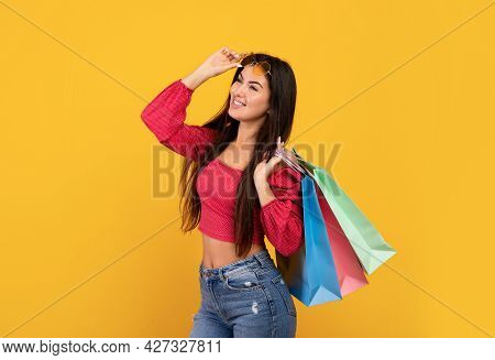 Seasonal Sales. Happy Armenian Lady Carrying Bright Shopper Bags And Looking At Free Space On Yellow