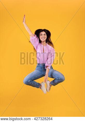Joyful Armenian Woman Jumping And Touching Legs With Hand, Yellow Studio Background, Full Length Pho