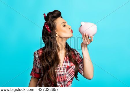 Portrait Of Glamorous Young Pinup Woman In Retro Style Clothes Kissing Piggy Bank On Blue Studio Bac