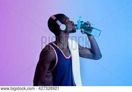 Young Black Sportsman With Bath Towel And Headphones Drinking Water From Bottle In Neon Light