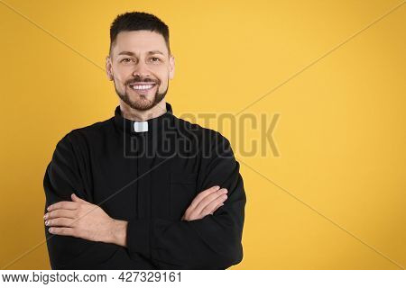 Priest Wearing Cassock With Clerical Collar On Yellow Background, Space For Text