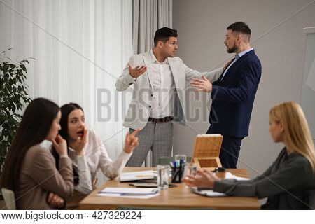 Angry Coworkers Quarreling At Workplace In Office