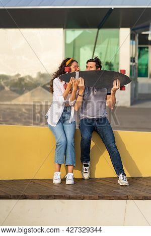 Street Fashion Couple Enjoy Summer In Outdoor Skate Park Sit Holding Longboard Together. Hipster Tre