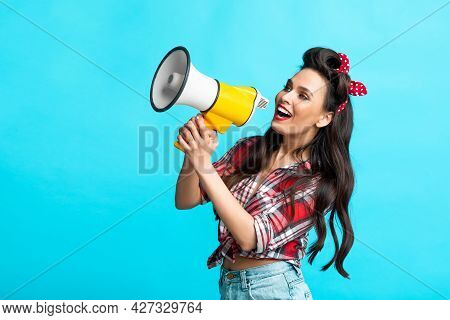 Sexy Pin Up Woman Shouting Into Megaphone, Advertising Something, Making Announcement On Blue Studio