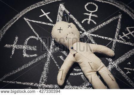 Voodoo Doll In Ritual Circle Drawn On Black Table, Closeup