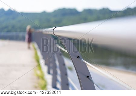 A Tubular Metal, Curved, Horizontal Fence On The River Embankment With A Standing Person On A Sunny