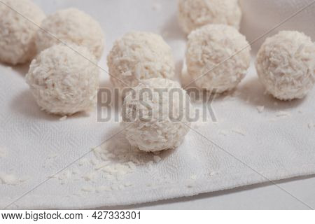 Coconut Balls On A White Table With A White Napkin, Round Sweet Candies  With Coconut Flakes, Vegan