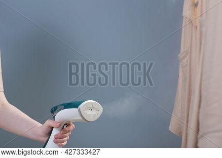 Female Hand With Steamer And Shirt On Blue Background