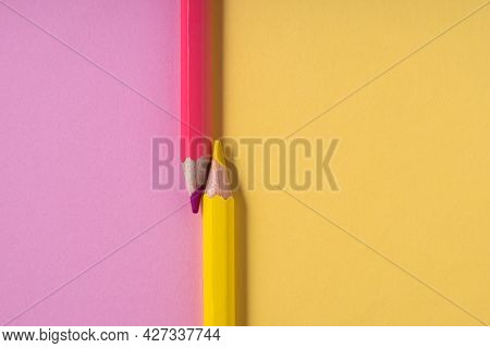 Pink And Yellow Pencils On Pastel Pink And Yellow Contrast Background. Education Concept.top View.pl