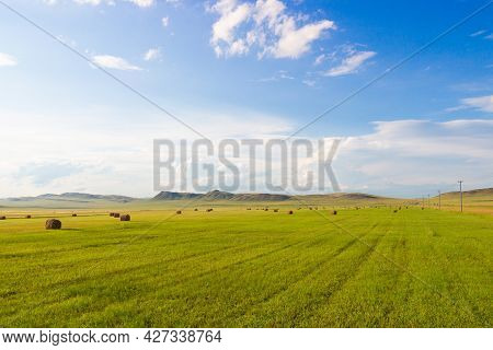 Summer Landscape With Hay Bales On Farming Fields Against The Background Of Awesome Cloudy Sky And G