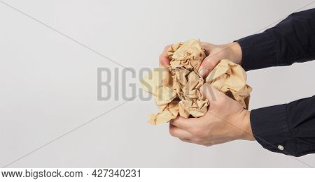 Crumpled Brown Paper.it Is Mauled In Man Hand On White Background.