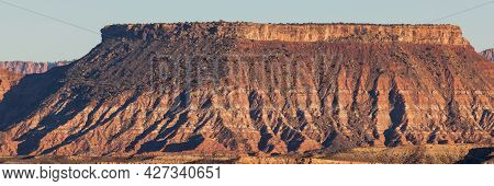 A High Plateau Of Eroding Sandstone With A Dark Square On The Left And White And Red Stripes To The