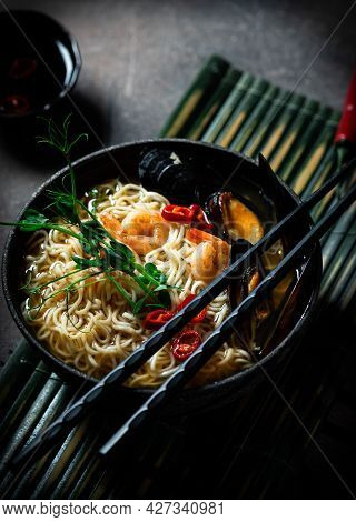 Traditional Japanese Soup Ramen With Shrimp, Asian Noodles, Mussels Chili Pepper On Dark Background.