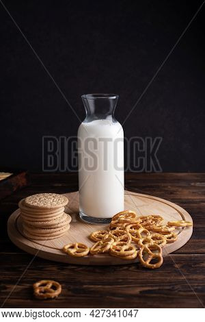 Milk Bottle With Cookies And Mini Salted Pretzels On A Dark Wooden Background, Breakfast And Snack,