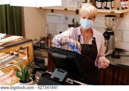 Mature woman wearing face mask wiping cash register in cafe