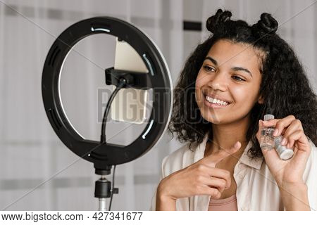 Black woman showing nail-polish while taking selfie footage on cellphone at home