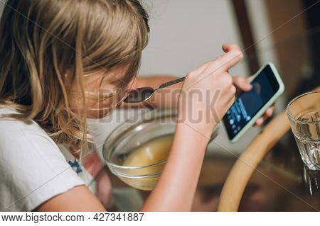 Teenage Girl Eating Breakfast And Looking At The Smartphone