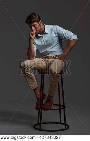 Young thoughtful and worried european businessman sitting on bar chair. Bearded man with dark hair wear shirt with trousers. Isolated on dark gray background. Studio shoot