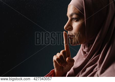 Young muslim woman in hijab showing silence gesture isolated over blue background
