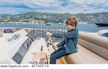 Captain Boy Drives The Yacht. Travel Adventure Concept. Yachting With Child On Summer Vacation. High