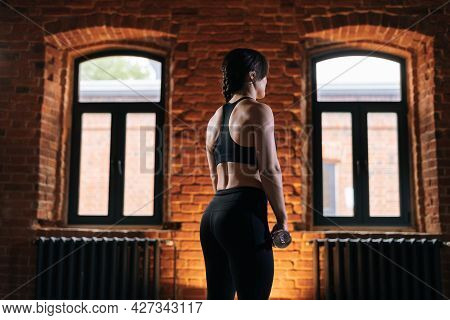 Medium Shot Of Rear View Of Young Athletic Woman With Beautiful Strong Body Wearing Activewear Holdi
