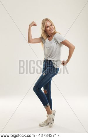 Young joking european girl posing like bodybuilder and looking at camera. Beautiful blonde female teenager with blue eyes wear white t-shirt and jeans. Isolated on white background. Studio shoot