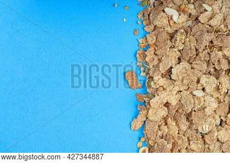Muesli. Close-up Of Muesli Scattered On A Table, Breakfast Cereals On A Blue Background. Healthy Foo
