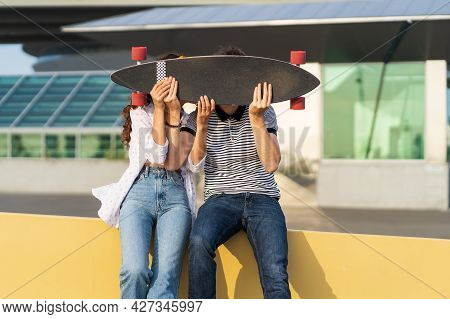 Romantic Couple Kissing Hiding Above Longboard Skate. Playful Man And Woman In Love Together Hold Sk