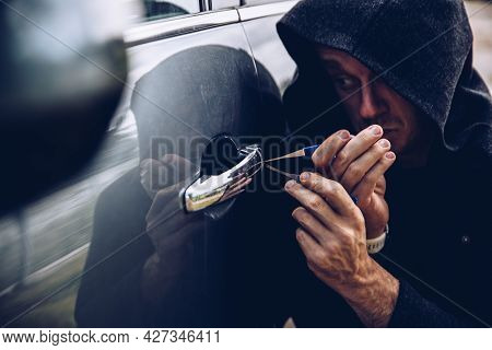 A Masked Thief Opening A Car Door With A Lockpicer.