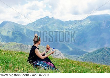 A Blonde Hiker Sits On The Grass, Eats And Drinks Water, Resting In The Beautiful Polish Mountains.