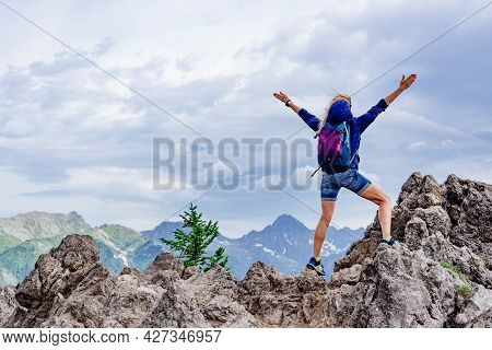 Woman Tourist Standing On A Rock With His Arms Spread Wide Looking In The Distance.
