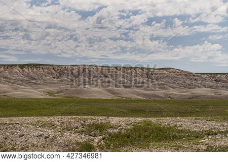 Badlands National Park, Sd, Usa - June 1, 2008: Beige Table Ridge With Footings On Horizon Under Blu