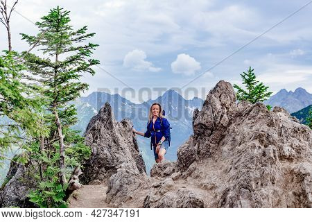 Smiling Hiker Is Standing On The Mountain Trail In The High Mountains.