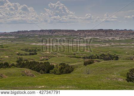 Badlands National Park, Sd, Usa - June 1, 2008: Vast Green Landscape With Geologic Table Ridge On Ho
