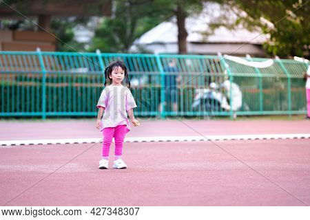 Happy Asian Child Standing On The Stadium. Girl Looking  At Front Of Her. Kid Wearing Pink T-shirt A