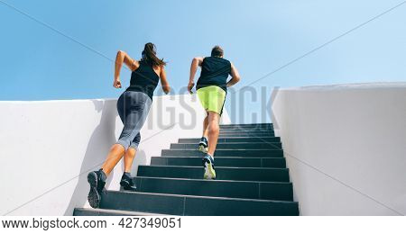 Stairs runners running up staircase training hiit workout. Couple working out legs and cardio at fitness gym. Healthy active lifestyle sport people exercising climbing staircase in urban city.