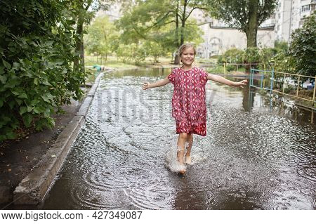 Cute Kids Jumping And Swimming In The Puddles After Warm Summer Rain, Outdoor Walking In Any Weather