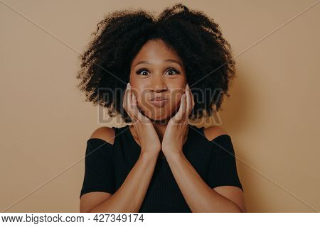 Cute African Woman With Wavy Hairstyle Making Funny Face, Puffs Out Her Cheeks And Holds Them With H