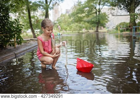 Cute Happy Kids Playing With Paper Boat In The Puddles After Warm Summer Rain, Outdoor Walking In An