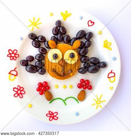 Edible Hedgehog Made Of Pancake With Grapes And Currant For Kids. Plate With Funny Pancake. Funny Br