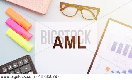 The Text Aml - Anti-money Laundering, On Office Desk With Calculator, Markers, Glasses And Financial