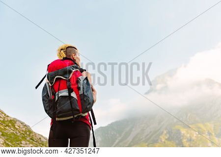 Young Girl With Red Backpack Observing The Landscape During A Trek Through The Mountains. Mountain A