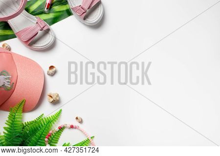 Flat Lay With Summer Accessories. Girls Accessories, Pink Sandals And Cap With Green Palm Leaves And