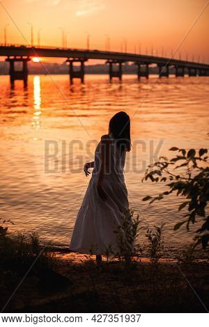 The Silhouette Of A Woman Dancing At Sunset. Lifestyle Full-length Portrait Of A Slender Woman Danci